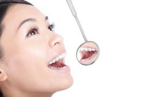 Woman with mouth open and a dental mirror against a white background