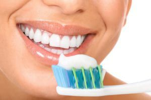 Woman smiling with a toothbrush in front of her mouth