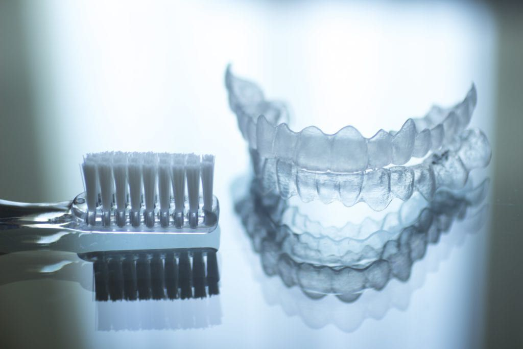 clear aligner next to a toothbrush